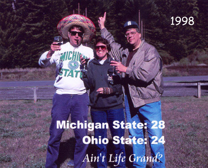 Photograph of artist Barbara Bromley, her husband (right) and brother (left) celebrating the Spartan victory over OSU in 1998 collegiate football